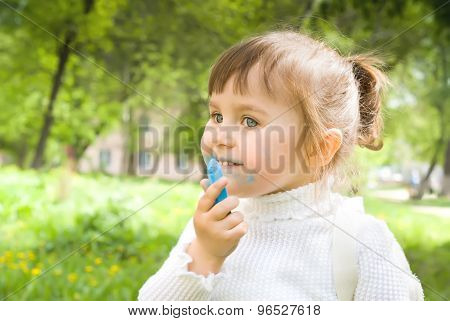 Cute little hellion girl with blue chalk outdoors