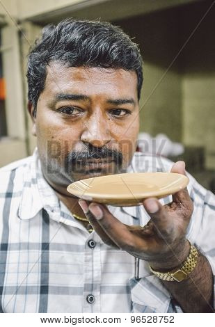 MUMBAI, INDIA - 05 FEBRUARY 2015: Portrait of Indian man drinks milk tea in traditional style. Post-processed with grain, texture and colour effect.