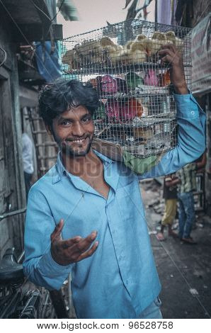 MUMBAI, INDIA - 10 JANUARY 2015: Indian worker carrying cage full of young poultry. Post-processed with grain, texture and colour effect.