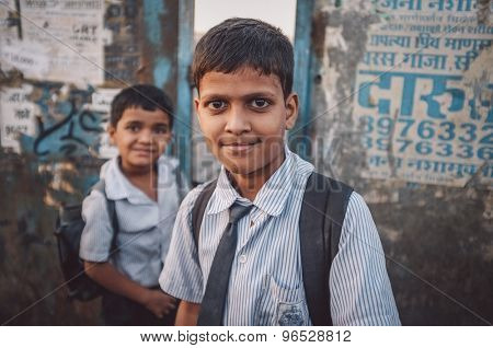 MUMBAI, INDIA - 12 JANUARY 2015: Indian school boys on bridge in Dharavi slum. Post-processed with grain, texture and colour effect.