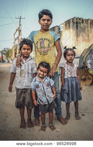 HAMPI, INDIA - 31 JANUARY 2015: Three young Indian boys and little girl standing in dusty street. Post-processed with grain, texture and colour effect.