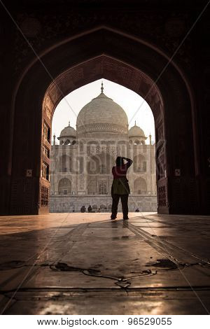 AGRA, INDIA - 28 FEBRUARY 2015: View of Taj Mahal from mosque. Woman photographing Taj. West side.