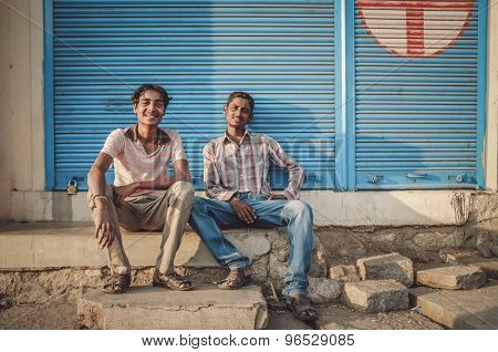 KAMALAPURAM, INDIA - 02 FABRUARY 2015: Local young Indian men sit in front of closed shop in a town close to Hampi. Post-processed with grain, texture and colour effect.