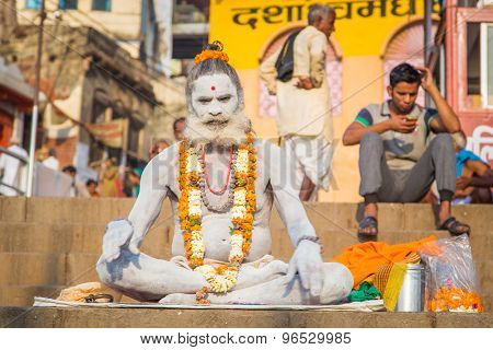 VARANASI, INDIA - 23 FEBRUARY 2015: Sadhu sits on ghat with legs crossed. Sadhu is a religious ascetic or holy person.