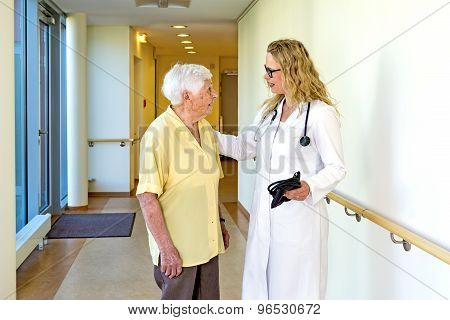 Doctor Talking To Elderly At The Hospital Corridor