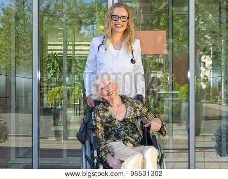 Happy Nurse And Elderly Patient Smiling At Camera