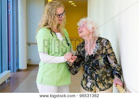 Therapist Assisting Elderly Walking In Hospital