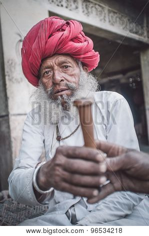 GODWAR REGION, INDIA - 12 FEBRUARY 2015: Elderly Rabari tribesman with traditional turban, clothes and long beard hands out chillum. Post-processed with grain, texture and colour effect.