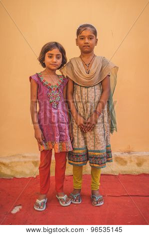 GODWAR REGION, INDIA - 15 FEBRUARY 2015: Two Indian girls pose in front of wall on red carpet. Post-processed with grain, texture and colour effect.