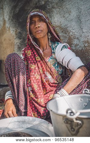 GODWAR REGION, INDIA - 13 FEBRUARY 2015: Rabari tribeswoman in sari decorated with traditional upper-arm bracelets cleans dishes. Post-processed with grain, texture and colour effect.