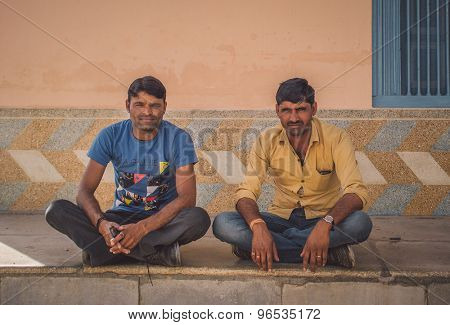 GODWAR REGION, INDIA - 15 FEBRUARY 2015: Two Indian men sit cross-legged on ground in front of home. Post-processed with grain, texture and colour effect.