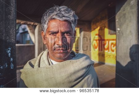 GODWAR REGION, INDIA - 14 FEBRUARY 2015: Adult Indian man with grey hair stands in street. Post-processed with grain, texture and colour effect.