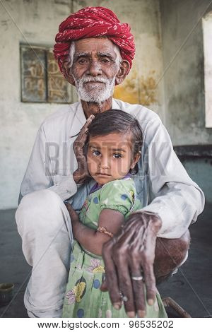 GODWAR REGION, INDIA - 12 FEBRUARY 2015: Rabari tribesman sits and holds granddaughter. Post-processed with grain, texture and colour effect.