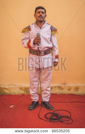 GODWAR REGION, INDIA - 15 FEBRUARY 2015: Indian musician dressed in wedding ceremony outfit holds microphone. Post-processed with grain, texture and colour effect.