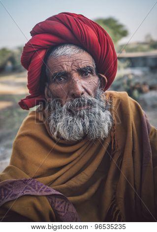 GODWAR REGION, INDIA - 14 FEBRUARY 2015: Elderly Rabari tribesman with red turban and blanket around the shoulders. Post-processed with grain, texture and colour effect..