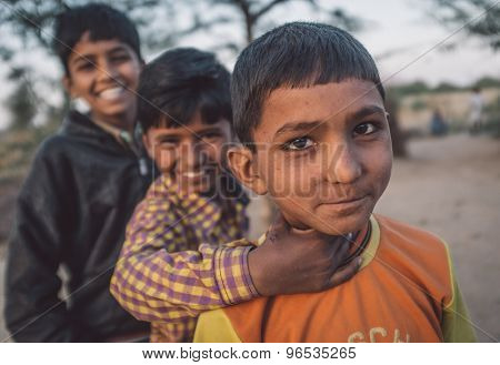 GODWAR REGION, INDIA - 12 FEBRUARY 2015: Three boys from Rabari tribe. Loss of tradition gains pace from every new generation. Post-processed with grain, texture and colour effect.