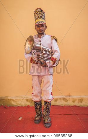 GODWAR REGION, INDIA - 15 FEBRUARY 2015: Indian musician dressed in wedding ceremony outfit holds trumpet. Post-processed with grain, texture and colour effect.