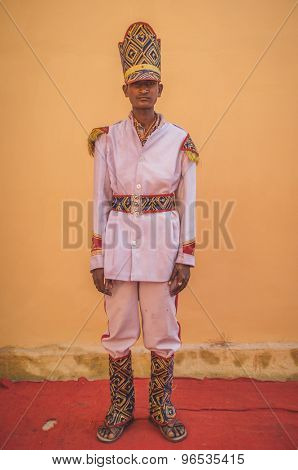 GODWAR REGION, INDIA - 15 FEBRUARY 2015: Young Indian musician dressed in wedding ceremony outfit with tall hat. Post-processed with grain, texture and colour effect.