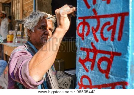 JODHPUR, INDIA - 07 FEBRUARY 2015: Man painting sign on column. Indian shop and store signs are mostly painted on walls, columns and panels. They are rarely digitally printed.