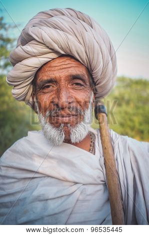 GODWAR REGION, INDIA - 14 FEBRUARY 2015: Elderly Rabari tribesman with white turban and blanket around the shoulders and ax. Post-processed with grain, texture and colour effect.