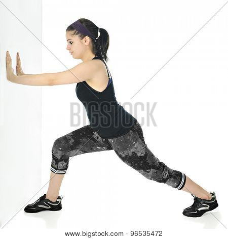 A pretty teen girl stretching her calves as she pushes against a wall and leans forward in a black and gray work outfit.  On a white background.