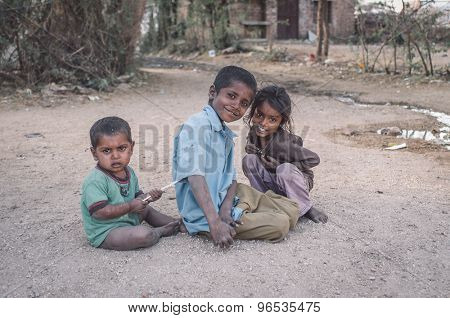 GODWAR, INDIA - 12 FEBRUARY 2015: Three kids sit and play on gravel ground in village street. Post-processed with grain, texture and colour effect.