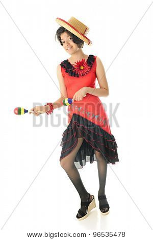 A young teen girl dancing in her red and black Mexican dress and hat, happily accompanying the beat with colorful maracas.  On a white background.