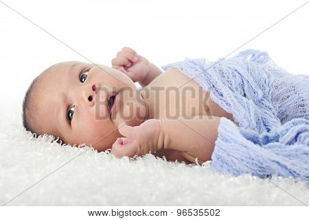 Close-up image of a newborn boy laying on his back swaddled in blue.  He has his eyes wide opened.  On a white background.