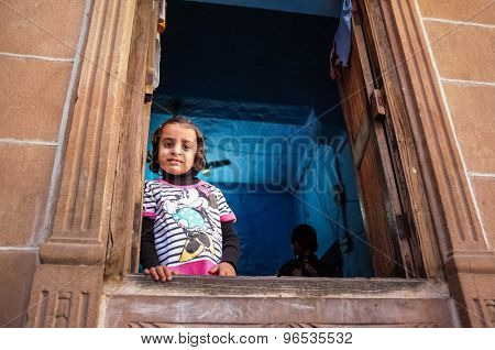 JODHPUR, INDIA - 07 FEBRUARY 2015: Little girl in Minnie Mouse shirt looking through window in blue-painted room. Common scene of blue-painted walls inside and outside of homes in old part of Jodhpur.