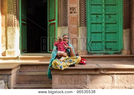 JODHPUR, INDIA - 07 FEBRUARY 2015: Grandmother in colorful sari sitting in front of home holding grandchild.