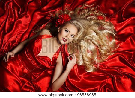 Hair Model, Fashion Woman Blonde Lying On Red Silk Cloth, Girl Posing With Long Curly Hairstyle