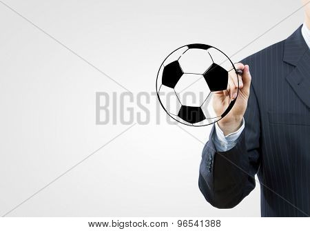 Close up of businessman hand drawing soccer ball