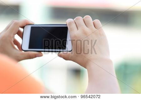 closeup of young woman hands use smart phone in city