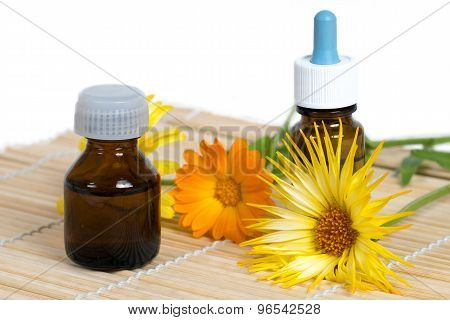 Two Bottle And Calendula Flowers On Bamboo Plate