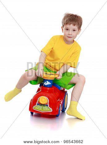 little boy rides his car