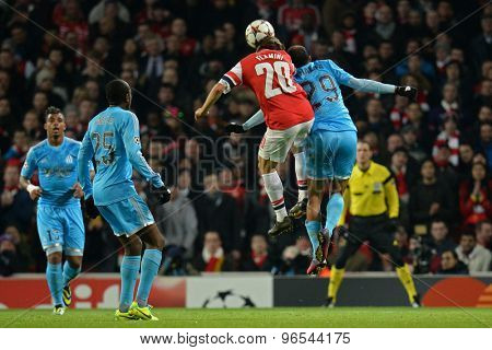 LONDON, ENGLAND - Nov 26 2013: Arsenal's Mathieu Flamini and Marseille's Saber Khalifa compete for the ball during the UEFA Champions League match between Arsenal and Olympique de Marseille,