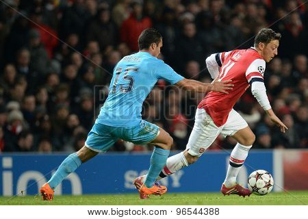 LONDON, ENGLAND - Nov 26 2013: Marseille's Jeremy Morel and Arsenal's Mesut Ozil compete for the ball during the UEFA Champions League match between Arsenal and Olympique de Marseille