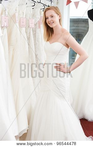 Bride Trying On Wedding Dress In Bridal Boutique