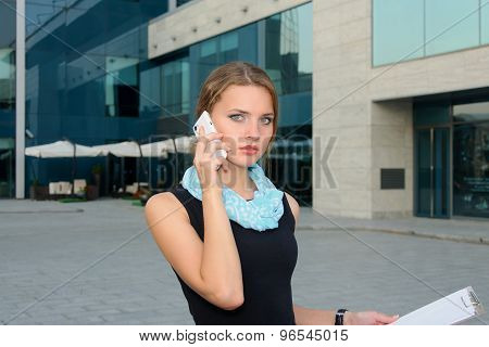 Business Woman With A Folder In Her Hand, Talking On The Phone