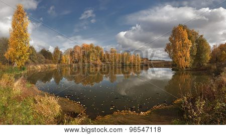 Forest Lake with yellow autumn trees and blue sky