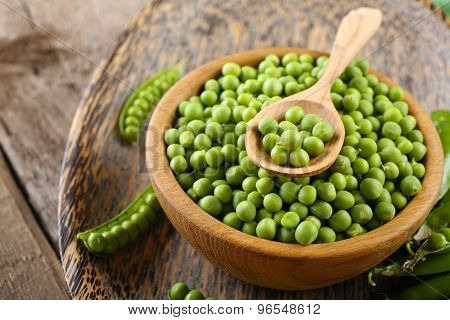 Fresh green peas in bowl on wooden tray, closeup
