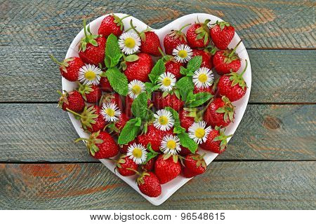 Red ripe strawberries on heart shaped plate, on color wooden background