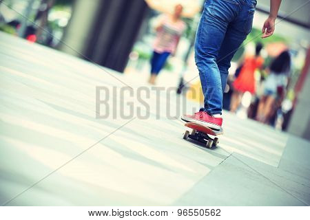young woman skateboarder riding on skateboard on city