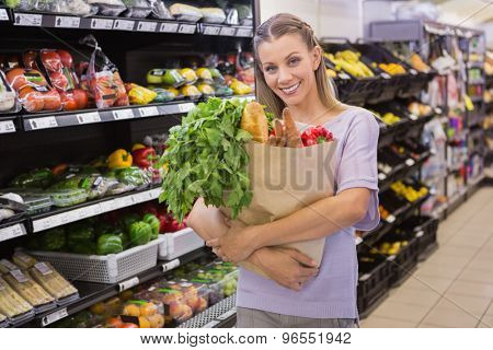 Pretty blonde holding bag with bread and vegetable in supermarket
