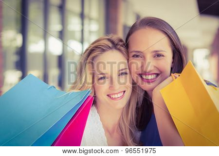 Portrait of happy smiling friends holding shopping bags