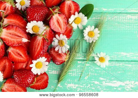 Strawberry with chamomile, leaves and ears on color wooden background
