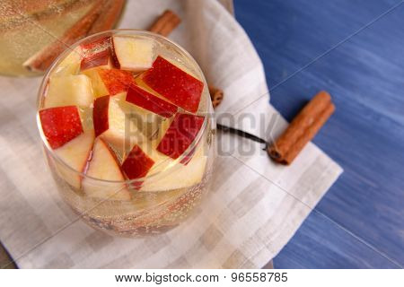 Glass of apple cider with fruits and spices on table close up