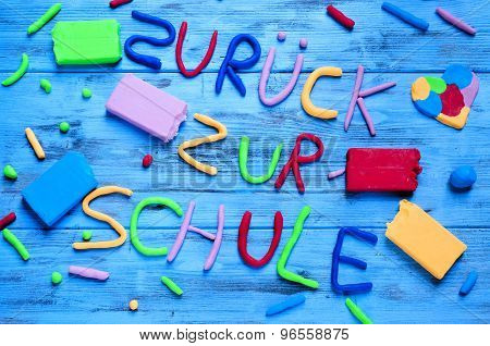 the sentence zuruck zur schule, back to school in german, written with modelling clay of different colors on a blue rustic wooden background