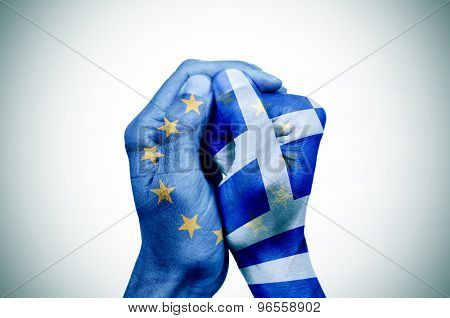 hand patterned with the flag of the European Community envelops another hand patterned with the flag of Greece