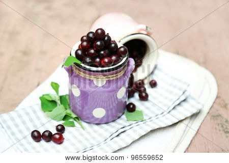 Red gooseberry in pail on wooden table close-up outdoors